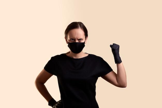 拳とベージュの壁を示す黒いドレスのフェイスマスクとラテックス手袋の怒っている女性