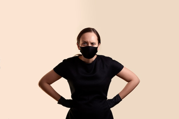 黒のドレスのフェイスマスクとベージュの壁の上に腕を腰に当てて立っているラテックス手袋の怒っている女性