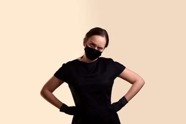 黒のドレスフェイスマスクとラテックス手袋を着用した怒っている女性が、頭を下げてベージュの壁を越えて腕を腰に当てて立っている