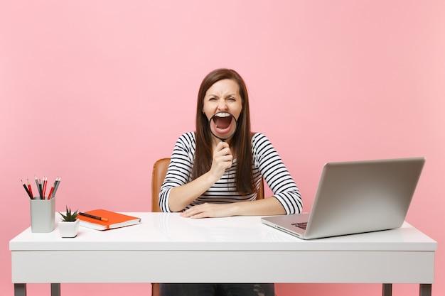 パステルピンクの背景に分離された現代的なpcのラップトップと白い机に座って拡大鏡を持って叫んでカジュアルな服を着て怒っている女性。業績ビジネスキャリアコンセプト。スペースをコピーします。