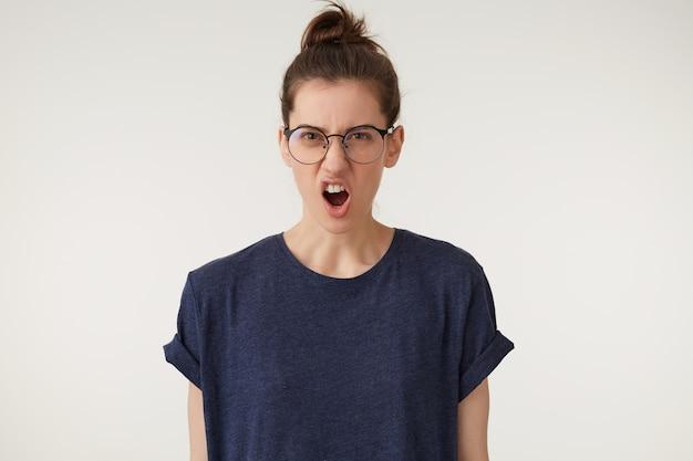 彼女の顔に不機嫌そうなしかめっ面、口を開いて眼鏡をかけている怒っている女性