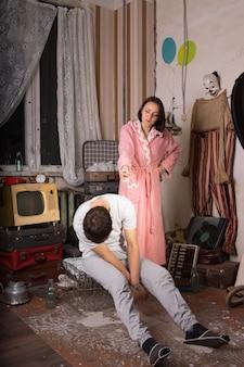 散らかった部屋で彼女の座っている眠っているパートナーを指しているピンクのローブの怒っている女性。
