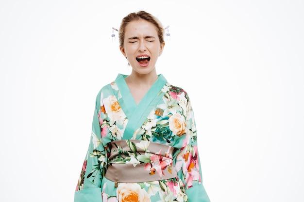 白で叫んで叫んでいる伝統的な日本の着物の怒っている女性