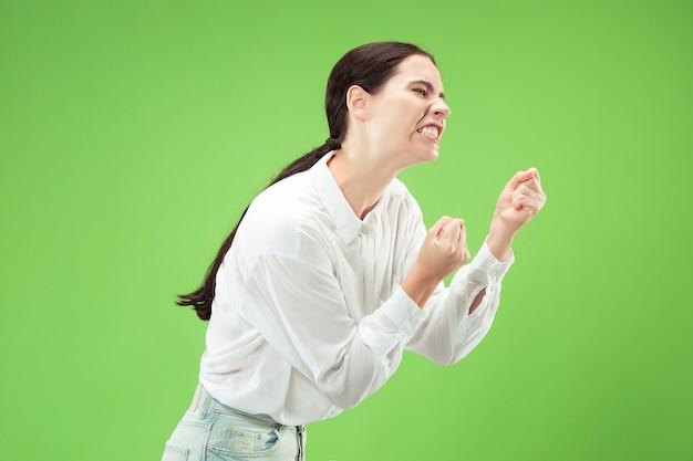 カメラを見ている怒っている女性。トレンディな緑地に孤立して立っている積極的なビジネス女性