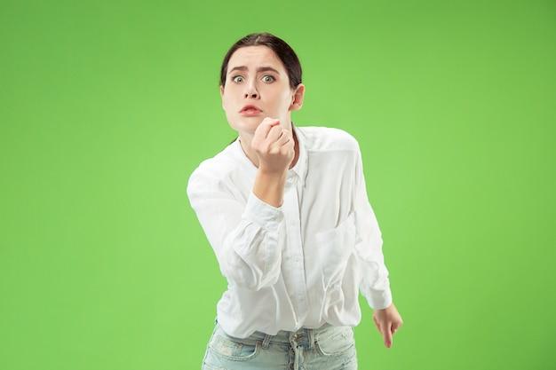 カメラを見ている怒っている女性。トレンディな緑のスタジオの背景に孤立して立っている積極的なビジネス女性。女性の半身像。人間の感情、表情の概念