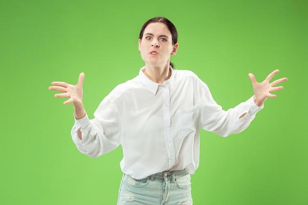 カメラを見ている怒っている女性。トレンディな緑のスタジオの背景に孤立して立っている積極的なビジネス女性。女性の半身像。