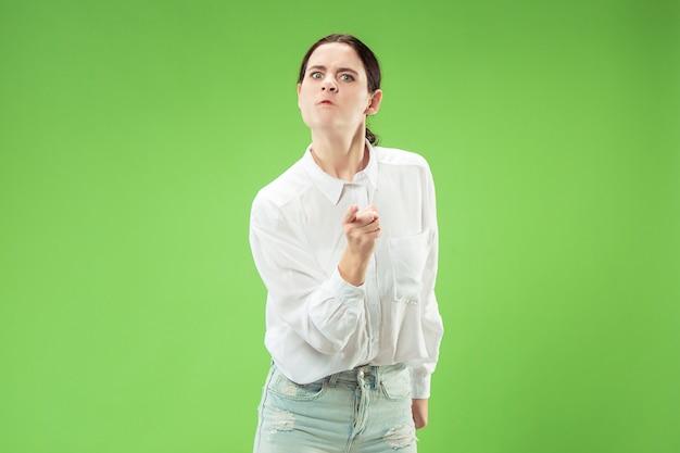 Сердитая женщина, смотрящая на камеру. агрессивное положение женщины дела изолированное на предпосылке модной зеленой студии.