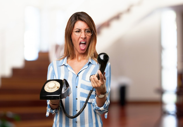 携帯電話を見て怒っている女性