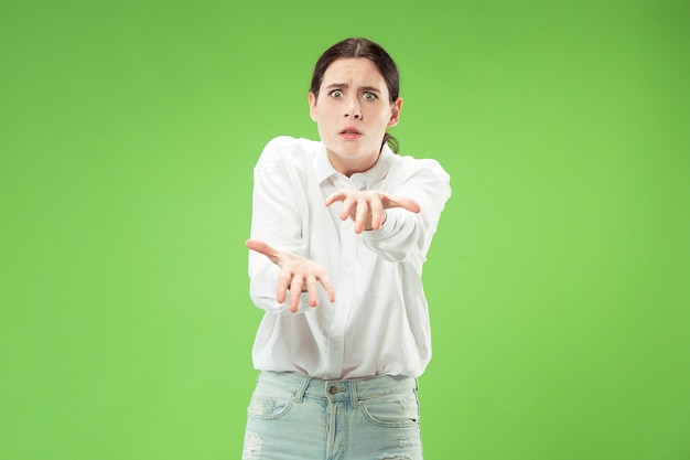 Angry woman looking at camera. aggressive business woman standing isolated on trendy green  space