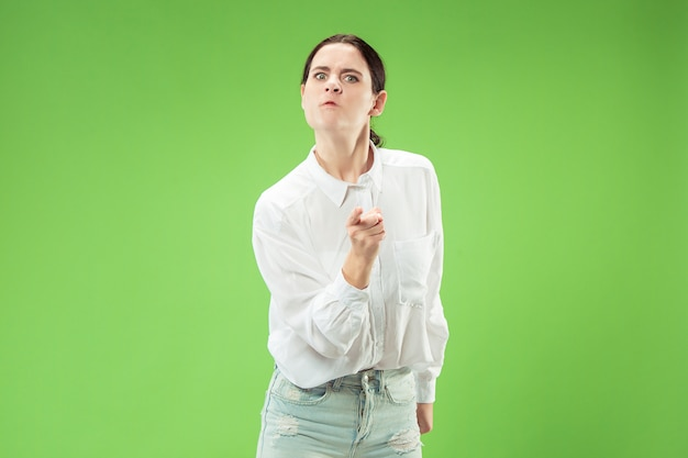 Donna arrabbiata che guarda l'obbiettivo. donna d'affari aggressiva in piedi isolato su sfondo verde alla moda per studio.