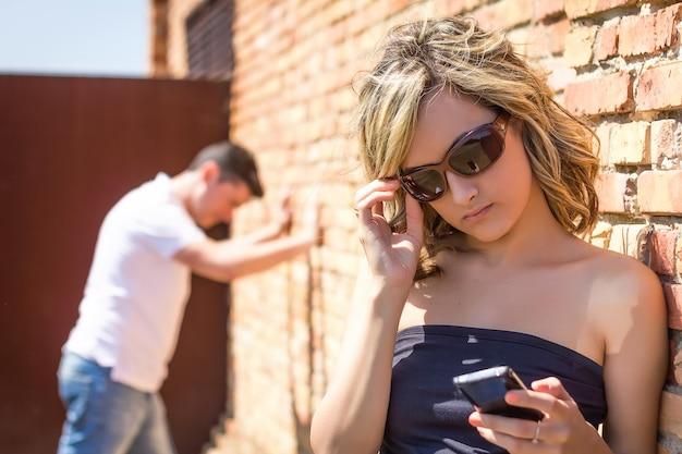 Злая женщина ищет телефон и мужчина позирует на стене