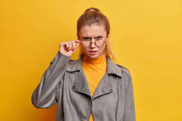 怒っている女性は透明な眼鏡を通して綿密に見え、何かに同意せず、灰色のジャケットを着て、ポーズをとる