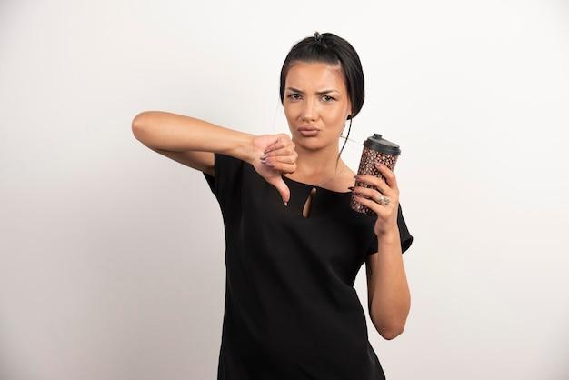 コーヒーの味のために親指を立てる怒っている女性。