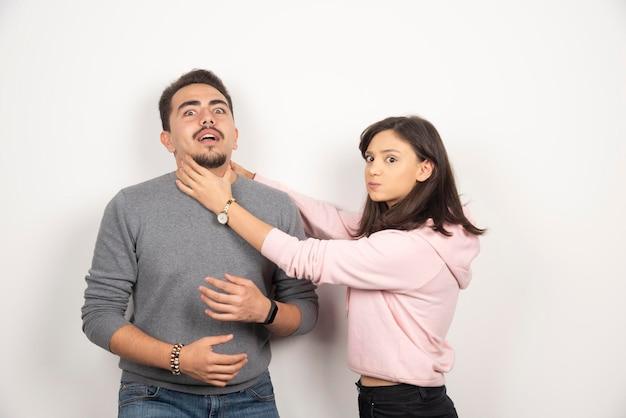 그의 남자 친구를 장난스럽게 질식시키는 화난 여자.