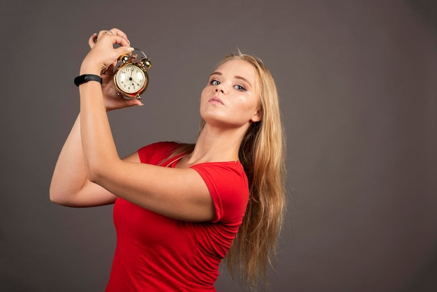 Сердитая женщина позирует с часами на темном фоне. фото высокого качества