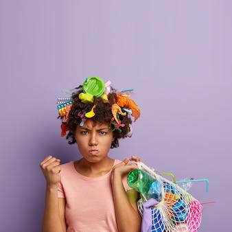 Donna arrabbiata in posa con immondizia tra i capelli