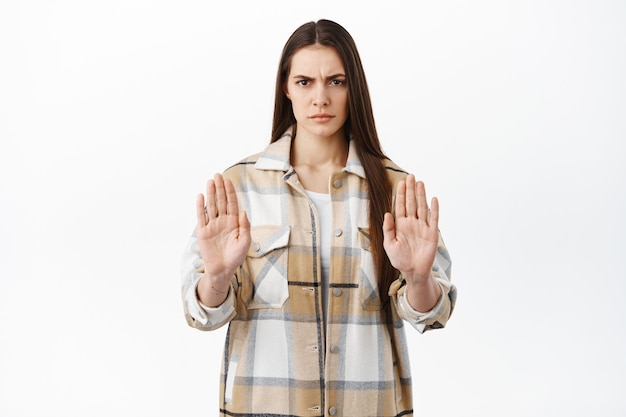 Angry woman say no, shows stop block gesture, refuse or reject something bad, decline offer, prohibit, tell to stay away keep social distance, standing over white wall