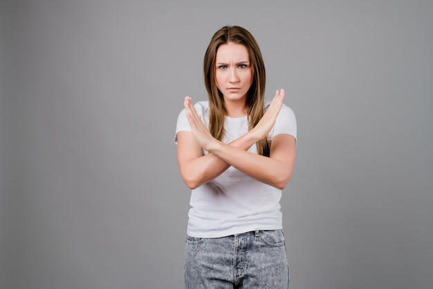 Angry woman saying no with hands crossed isolated on grey