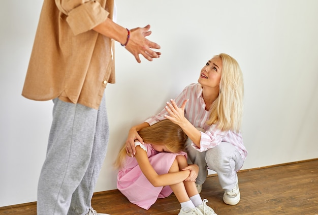 Angry woman scream at husband humiliating daughter, she sits on the floor