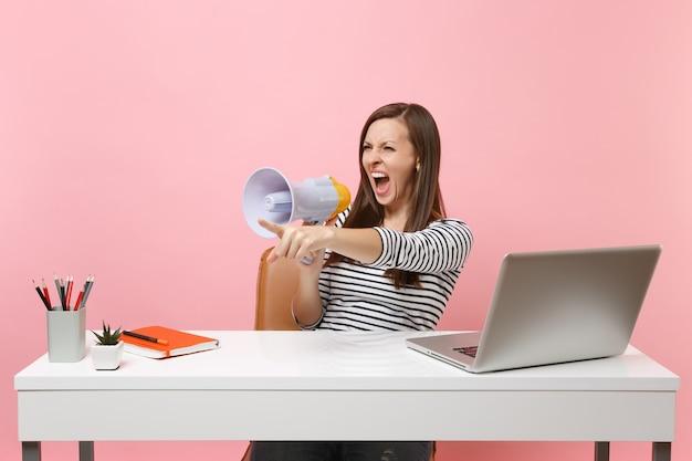パステルピンクの背景に分離されたpcラップトップと白い机で働いて人差し指を指しているメガフォンで叫んで怒っている女性。業績ビジネスキャリアコンセプト。広告用のスペースをコピーします。