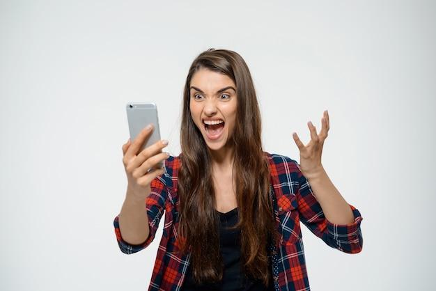 Сердитая женщина кричит на мобильный телефон