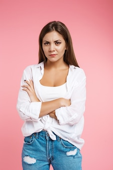 Angry woman shows irritation looking straight without smile