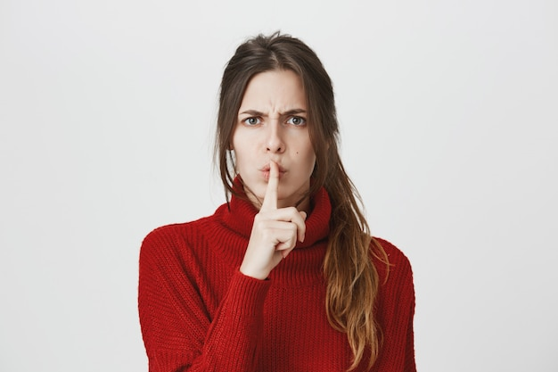 Angry woman shushing with finger pressed to lips