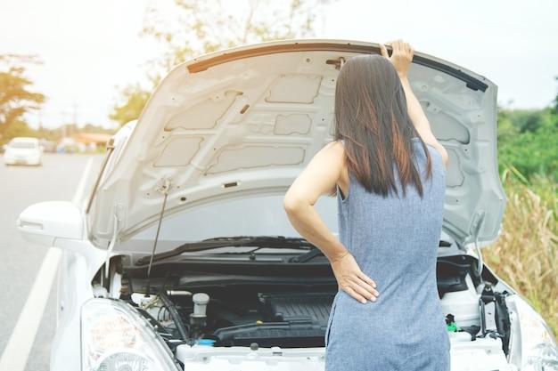 怒っている女性が助けを求めて壊れた車の前に立つ