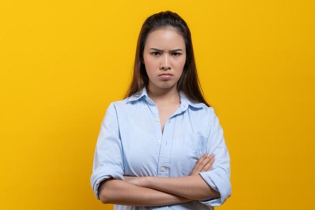 立っている怒っている女性は組んだ腕と黄色の背景に分離されたカメラを見つめます。