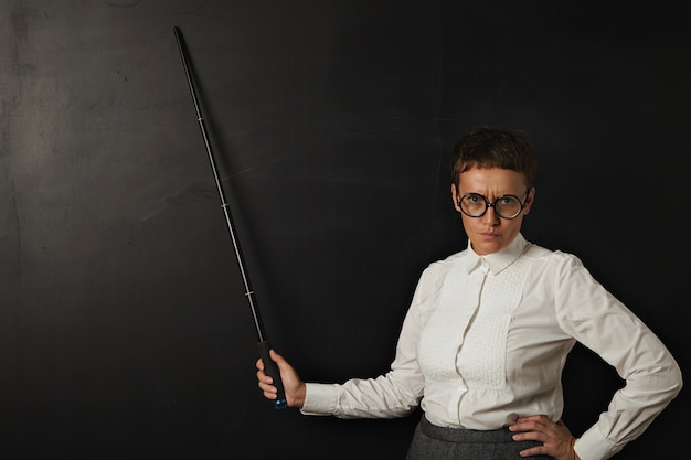 Angry woman teacher and shows on black chalk board behind her with folding pointer