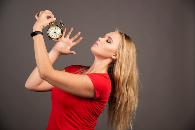 怒っている女性は黒い壁の時計をシャットダウンしたいと考えています。