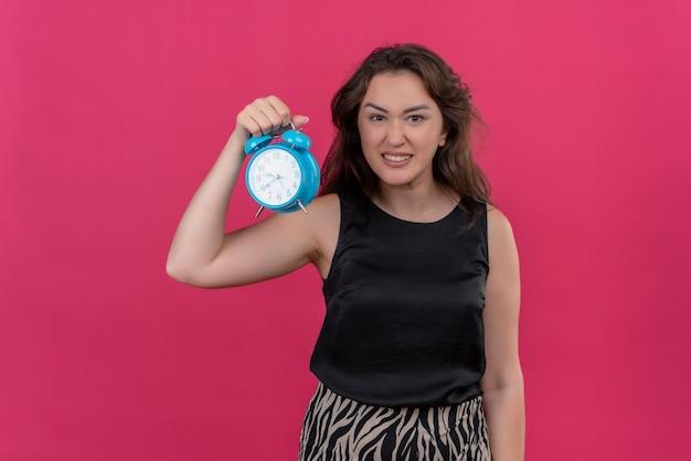 ピンクの壁に目覚まし時計を保持している黒いアンダーシャツを着て怒っている女性