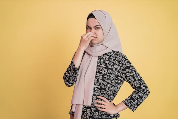 코를 덮고 한 손으로 허리를 잡고 서 있는 히잡을 쓴 화난 여자