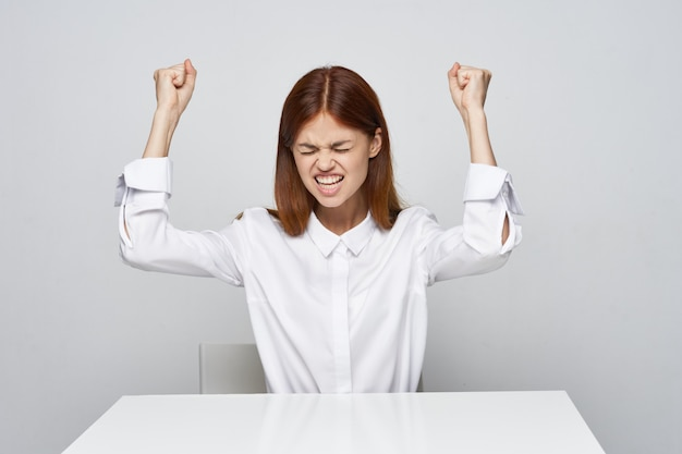 Angry woman in a white shirt on a light background