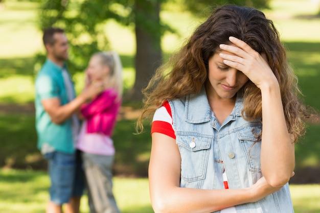 Злая женщина с мужчиной и подругой в фоновом режиме в парке