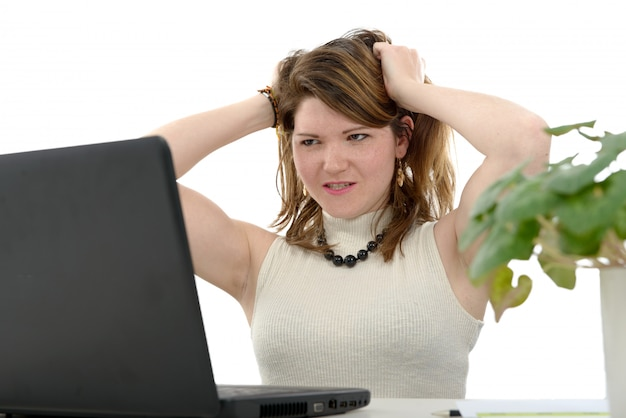 Angry woman working on laptop