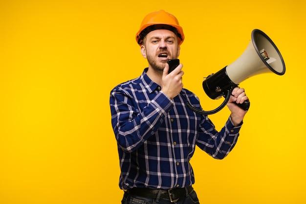 黄色のメガホンとオレンジ色のヘルメットの怒っている労働者の男-画像