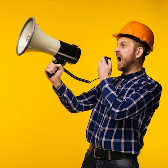 Angry worker man in orange helmet with a megaphone on yellow background