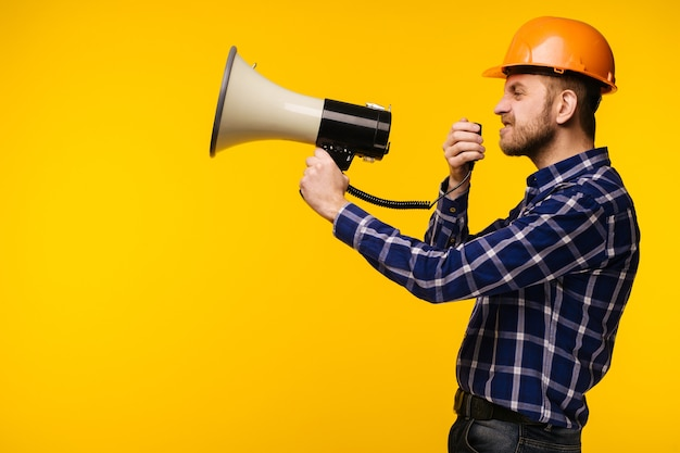 Angry worker man in orange helmet with a megaphone on yellow