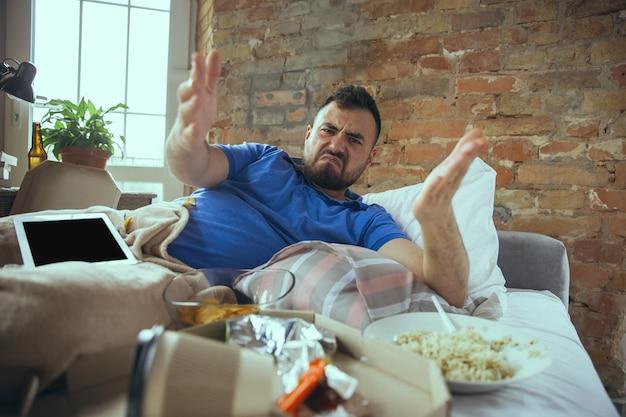 怒っている、wtf。散らかったベッドに住む怠惰な白人男性。幸せになるために外出する必要はありません。ガジェットを使用したり、映画やシリーズ、ソーシャルメディアを視聴したりすると、感情的に見えます。ホームライフスタイル。