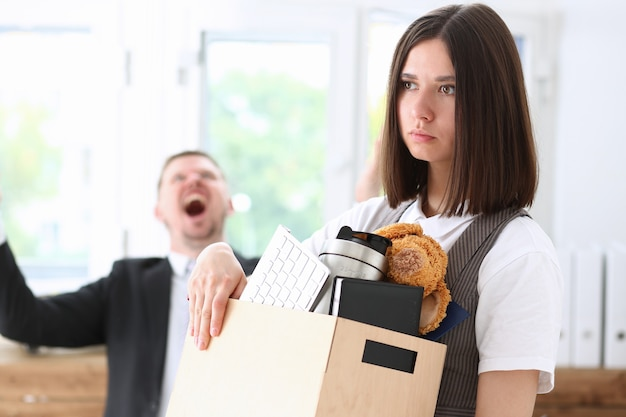 Angry yelling boss pointing arm to dismissing sad worker with stuff box portrait.