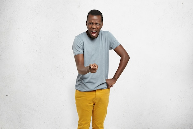 Arrabbiato giovane cliente afro-americano che punta il dito indice alla telecamera