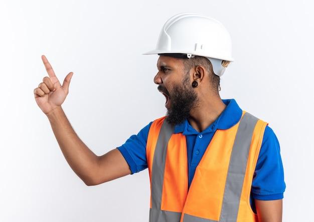 Сердитый молодой афро-американский строитель человек в форме с защитным шлемом кричит на кого-то, смотрящего в сторону, изолированную на белом фоне с копией пространства