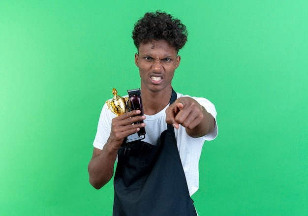 Angry young afro-american male barber wearing uniform holding cup winner and showing you gesture isolated on green background