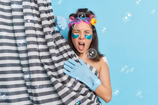 Angry young asian woman exclaims negatively takes shower applies collagen patches under eyes hair rollersand rubber gloves poses behind shower curtain takes douche isolated over blue background