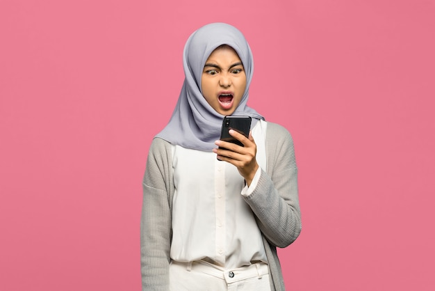 Angry young asian woman holding mobile phone with mouth opened