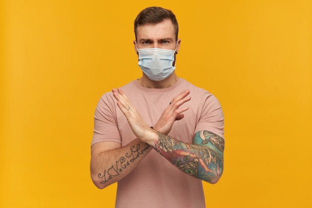 Angry young bearded man with tattoo on hand in pink tshirt and hygienic mask to prevent infection making x shape with arms and hands over yellow wall saying no and