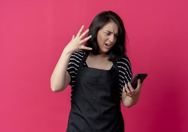 Сердитая молодая красивая женщина-парикмахер в фартуке смотрит на экран своего мобильного телефона с раздраженным выражением лица над розовым