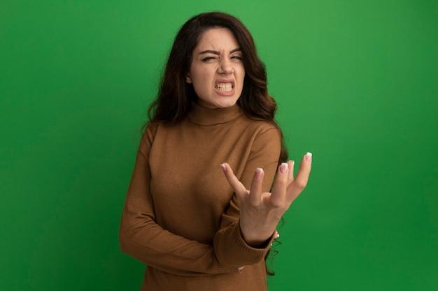 Giovane bella ragazza arrabbiata che dà la mano alla macchina fotografica isolata sul muro verde green