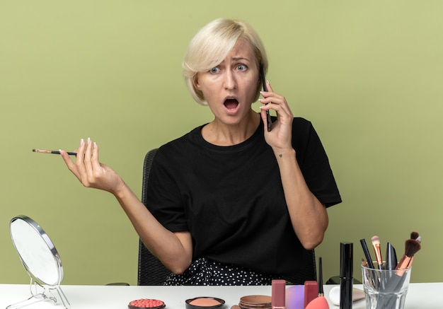 La giovane e bella ragazza arrabbiata si siede al tavolo con gli strumenti per il trucco parla al telefono tenendo il pennello per il trucco isolato sul muro verde oliva